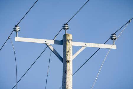 Photo pour Electricity mains supply close up, overhead power lines against a blue sky, UK - image libre de droit