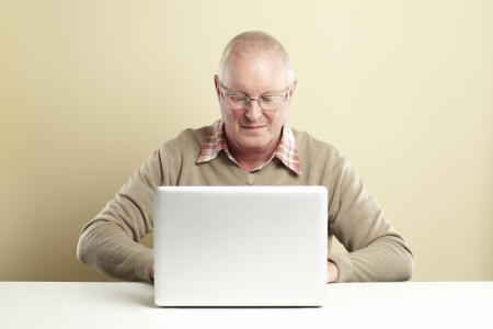 Senior man using laptop whilst smiling