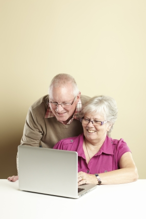 Senior man and woman using laptop whilst looking happy