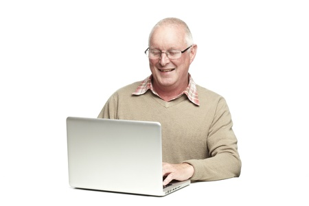 Senior man using laptop whilst smiling, on white background