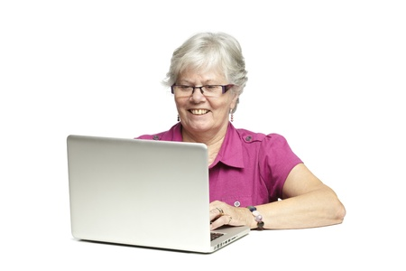 Senior woman using laptop whilst smiling, on white background