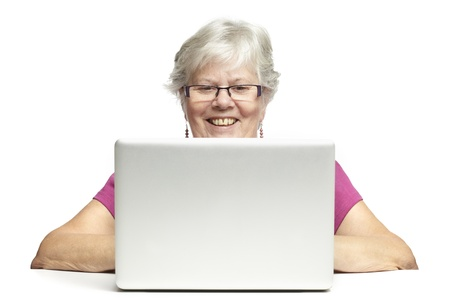 Senior woman using laptop whilst smiling, on white background