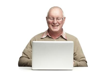 Senior man using laptop whilst smiling, on white background