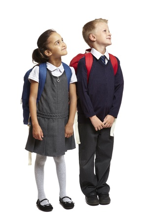 8 year old school boy and girl with backpacks looking up on white background