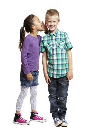 8 year old girl whispering in boys ear smiling on white background