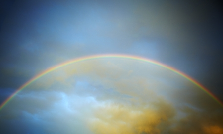 Rainbow infront of stormy sunset sky