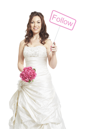 Bride wearing wedding dress holding a follow sign smiling on white background