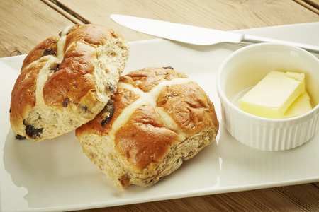 Hot cross bun on white dish and wooden table top