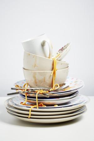 Dirty dishes pile needing washing up  Household chore concept on white background