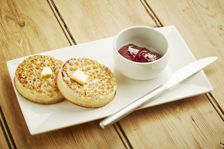 Crumpets toasted on white dish and wooden table top