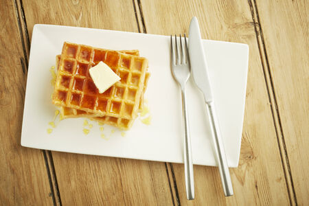 Waffles with syrup on white dish and wooden table top