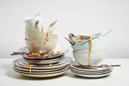 Dirty dishes pile needing washing up. Household chore concept on white background