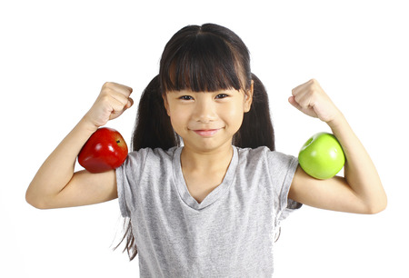 Foto de A little girl flexes her muscle while showing off the apple that made her strong and healthy - Imagen libre de derechos