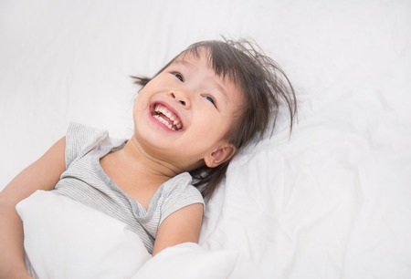 Adorable screaming little girl waked up in her bed