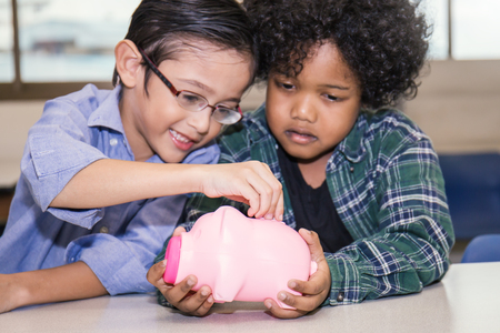 Little boys putting money into piggy bank for future savings
