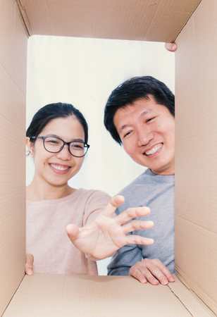 Asian couple man and woman looking into a cardboard box, Asian man and woman open the cardboard box her hand reaching inside the box with surprise expression on their face.