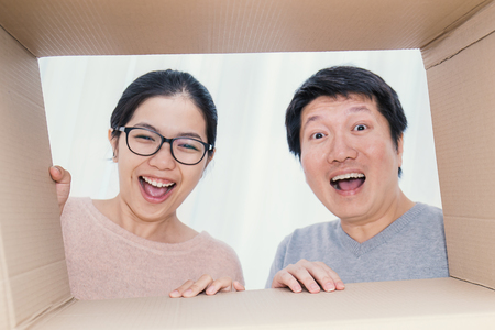 Asian couple man and woman looking into a cardboard box, Asian man and woman open the cardboard box with surprise expression on their face. (focus on hands)