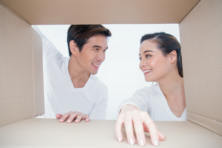 Portrait of Asian couple man and woman looking into a cardboard box, Asian man and woman open the cardboard box with surprise expression on their face.