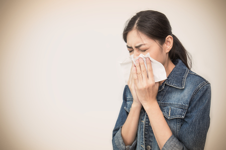 Photo pour Woman with a cold blowing her runny nose with tissue. Portrait of Asian beautiful girl get sick sneezing from flu. Healthcare and medical concept. - image libre de droit