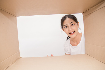 Portrait of Asian woman looking into a cardboard box, Asian woman open the cardboard box with surprise expression on their face.