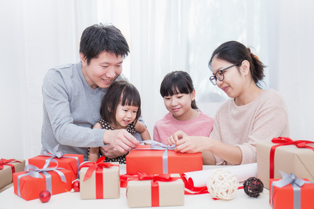 Foto de Asian little girl help her father and mother  wrapping gift box, celebration holiday christmas mother's day concept. Happy asian family unwrap gift boxed together. - Imagen libre de derechos