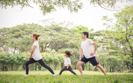 Foto de Family exercising and jogging together at the park. Group of family father mother and daughter stretching after sport on the grass. Sport health care and medical concept. - Imagen libre de derechos