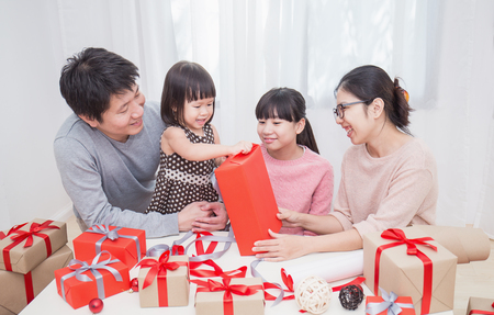 Foto de Asian little girl help her mother and father wrapping gift box, celebration holiday christmas mother's day concept. Happy asian family in Christmas season - Imagen libre de derechos