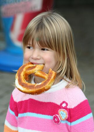 little girl eating a piece of bread with her hands