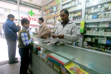 DELHI - FEBRUARY 2008. Pharmacy assistant selling medicine to customers on February 12, 2008 in Delhi, India. 80% of medicine revenue comes from international markets and just 20% from India.