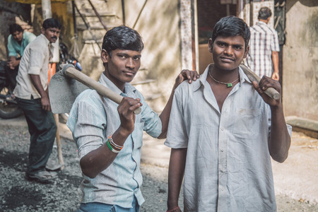 Photo pour MUMBAI, INDIA - 08 JANUARY 2015: Two young Indian workers stand in street with hoe's in hands. Young boys and girls work as cheap labor throughout India. - image libre de droit