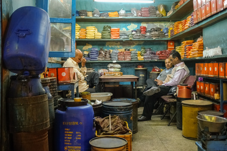 Photo for JODHPUR, INDIA - 07 FEBRUARY 2015: Owner of spice store massages forehead after long working day while customers discuss business. Long working hours are common in India. - Royalty Free Image