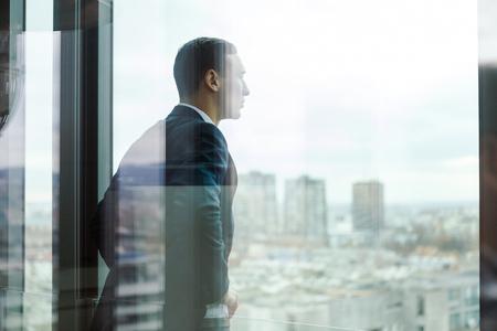 Photo pour Business man looking out through the office balcony seen through glass doors. - image libre de droit