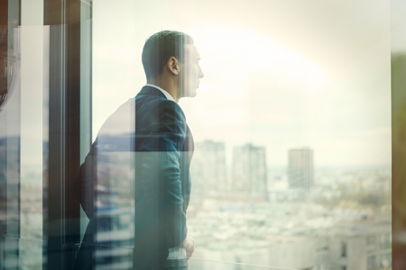 Photo for Business man looking out through the office balcony seen through glass doors. Post processed with vintage filter. - Royalty Free Image