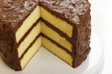 Photo pour A yellow layer cake with chocolate icing with a slice missing - image libre de droit