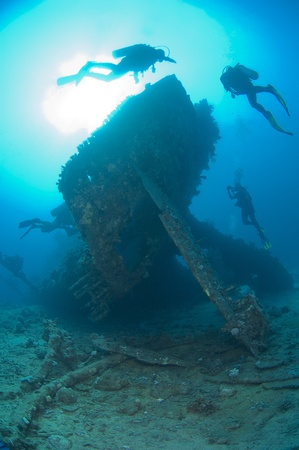 Scuba divers exploring the stern section of a shipwreck in the sun