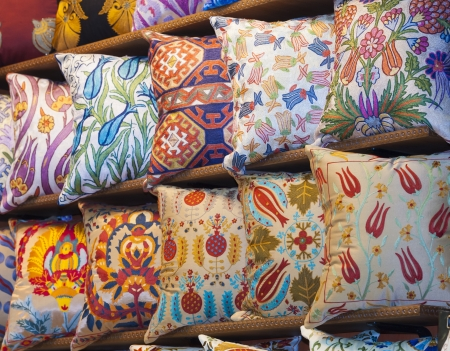 Display of ornately decorated cushions at an indoor market stall
