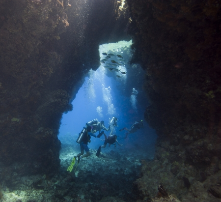 Scuba divers exploring an underwater sea cave in a tropical coral reef