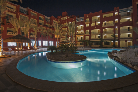 View over a swimming pool in luxury tropical hotel resort at night with date palm trees