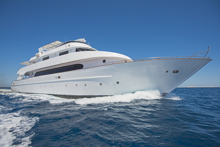 Photo pour Large luxury motor yacht under way sailing out on tropical sea ocean with blue sky background - image libre de droit