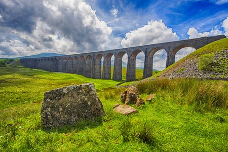 Foto de View of a large old Victorian railway viaduct across valley in rural countryside scenery panorama with stone wall - Imagen libre de derechos