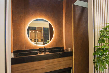 Photo for Interior design of a luxury show home bathroom with twin sinks and round mirror - Royalty Free Image