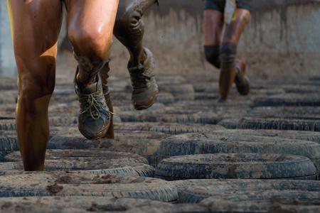 Photo pour Mud runners race, tries to make it through the pull trap - image libre de droit