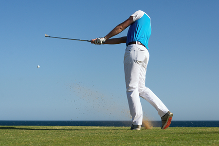 Photo pour Golfer hitting ball with force. The grass distribution and ball blurred. - image libre de droit