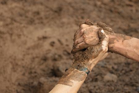 Photo pour Couple hold hands,help when overcoming hindrances mud - image libre de droit