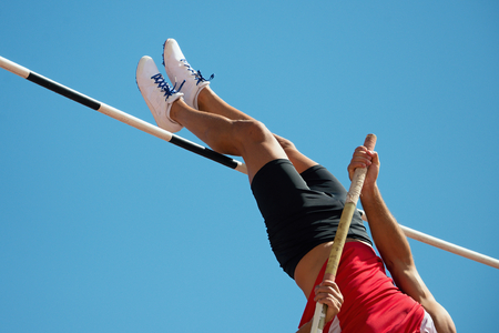 Athlete pole vault with a blue sky