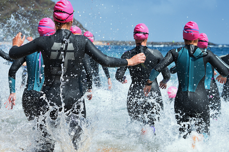 Photo pour Group triathlon participants running into the water for swim portion of race,splash of water and athletes running. - image libre de droit