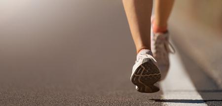 Foto de Running shoe closeup of woman running on road with sports shoes - Imagen libre de derechos