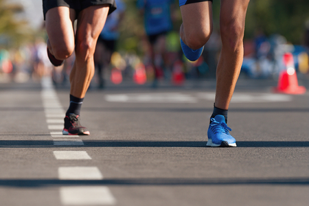 Foto de Marathon running race, people feet on city road - Imagen libre de derechos