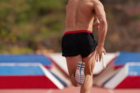 Man athlete performs the high jump pole vault