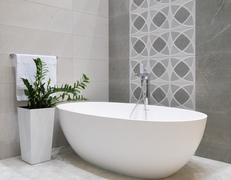 Photo pour modern bathroom interior design with white stone bathtub, grey tiles wall, ceramic flowerpot with green plant and hanger with towel - image libre de droit